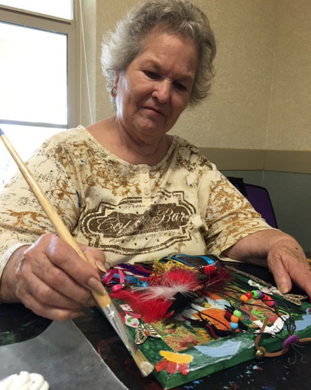 Resident working with her art